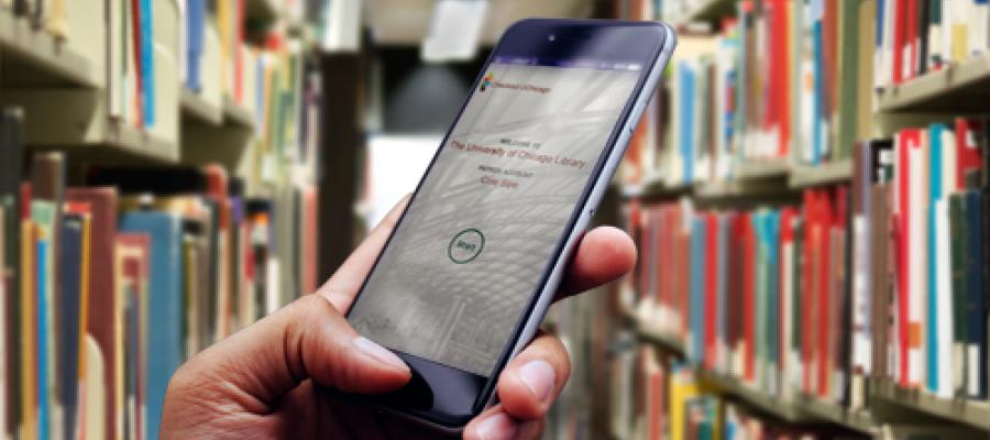 Student looking at phone in UChicago library